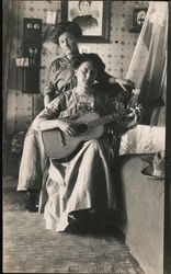 Two women with one playing a guitar Postcard