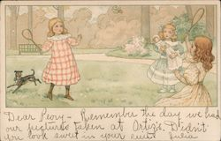 Two Girls playing badminton, while a third girl, with doll, watches Postcard