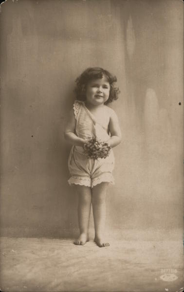 Little girl in white top and bloomers, holding flowers