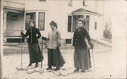 Three ladies pose while skiing, near houses, wearing dresses Postcard