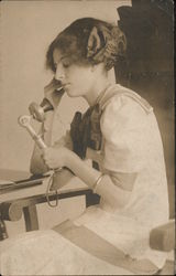Young woman sits and talks on a telephone Postcard