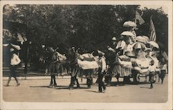 Horses, blankets, pulling a decorated cart full of people with flags and parasols. Postcard
