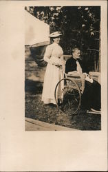 Young woman stands behind wheelchair of older woman Postcard