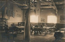 People in uniform sitting at tables inside a building
