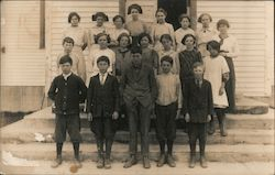 Children pose standing on the steps of a white building. Postcard