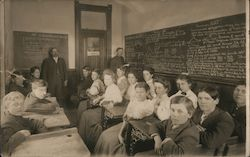 Students and teachers pose in a classroom with blackboards filled with math Postcard