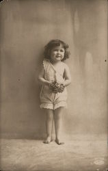 Little girl in white top and bloomers, holding flowers Postcard