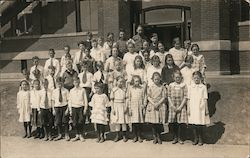 Children posing as a group outside a brick building Postcard