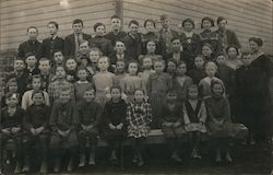 Group of children posing outside, with a teacher Postcard