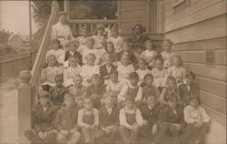 A class poses on the steps outside Postcard