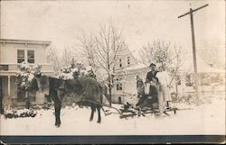 Family on sleigh with horse in front of houses Postcard