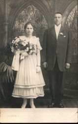 A Bride Holding Flowers Next to a Groom Postcard