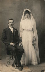 A Groom Sitting Next to his Standing Bride Postcard