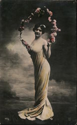Woman in see through sheath holding arch of flowers Postcard