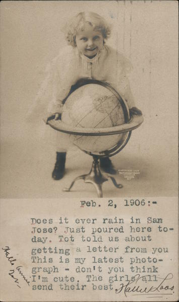Golden haired child standing over globe in stand California