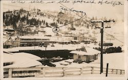 Train on track going through snow covered town Postcard