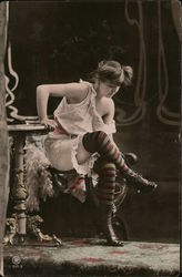 Girl in underthings sitting on arm of chair taking off shoes Postcard