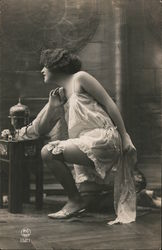 Woman posing with small table and lamp, stockings Postcard