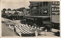 Parade of three large U.S. Flags carried by servicemen. Postcard
