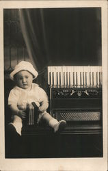 Little boy with toy accordion next to real accordion