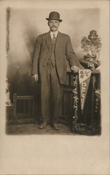Studio photo of well dressed man with hat standing next to California banner, flowers Postcard