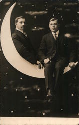Photo of two young men sitting on a crescent paper moon