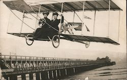 Two women flying in a biplane next to a pier (Studio Photo) Postcard