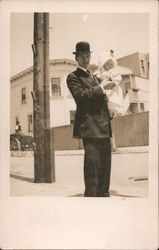 Man in bowler hat holding a baby Postcard