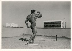 Arnold Schwarzenegger body building pose on rooftop, 1973