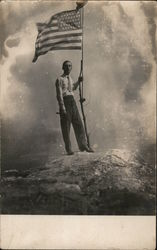 Man with American Flag on makeshift flagpole atop a rock Postcard