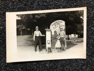 VTG RPPC POSTCARD, OSCODA, MI TWO AUSABLE RIVER HOGS DRINK FROM YE OLD TOWN PUMP