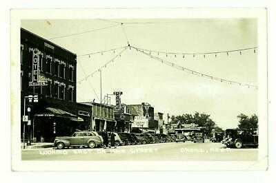 WWII NEBRASKA, O'NEILL LOOKING EAST ON MAIN STREET 1943 RPPC CARS MOVIE THEATER