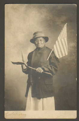 EARLY 1900S RPPC, BLACK LADY HOLDING AMERICAN FLAG, KNIFE & SHOVEL, CLEBRATING?
