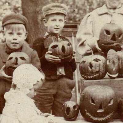 RPPC Halloween Kids Carving Jack O Lantern Spooky Pumpkin in Wicker Wheel Chair